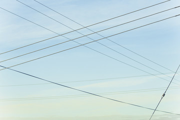 Power lines overhead, criss crossing in the air, at Belridge in California.