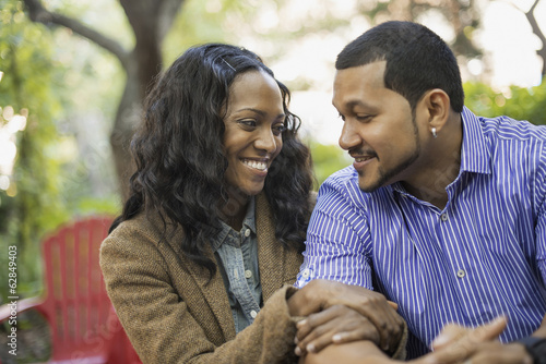 Scenes from urban life in New York City. A man and a woman, a couple with linked arms sitting side by side.