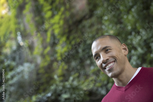Scenes from urban life in New York City. A man smiling, in a relaxed mood, in a leafy space.