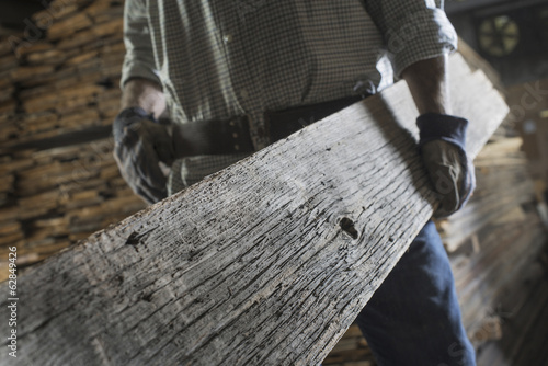 A heap of recycled reclaimed timber planks of wood. Environmentally responsible reclamation in a timber yard. A man carrying a large plank of mature weathered wood.