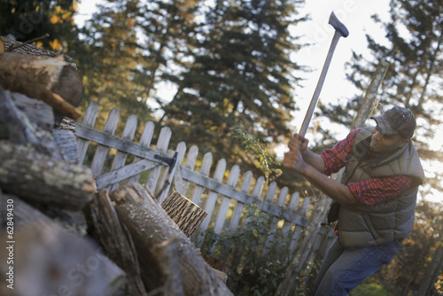A man wielding an axe, and chopping wood, splitting logs for the fire.