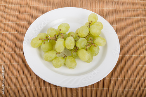 White grapes on white plate and bamboo platemat