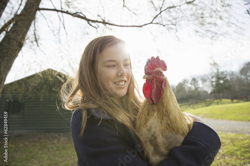 An animal sanctuary. A young girl holding a chicken with brown feathers and a red coxcomb.