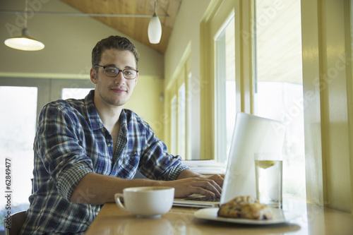 A young man sitting at a table using a laptop computer.