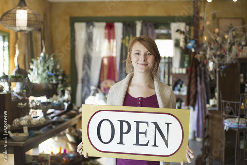 A woman standing in an antique store, holding an OPEN sign. Displays of goods all around her.