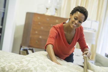 Woman straigtening bed with organic sheeting