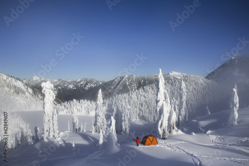 Michael Hanson walks through deep powder to his campsite in the snow covered Cascade Mountains overlooking Snow Lake.