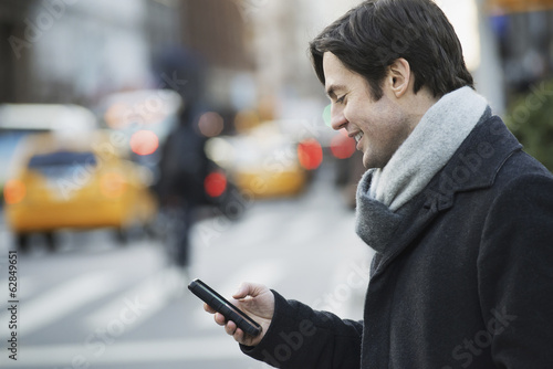 Man on busy street with smartphone
