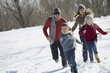 Winter scenery with snow on the ground. Family walk. Two adults chasing two children.