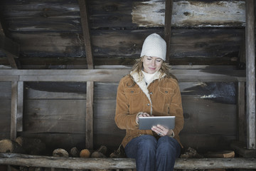 An organic farm in upstate New York, in winter. A woman sitting in an outbuilding using a digital tablet.