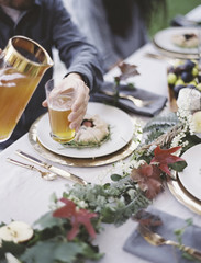 A group of people around a table in a garden. A celebration meal, with table settings and leafy decorations. A person pouring drinks into glasses.