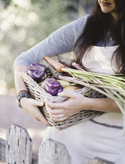 A young woman in a vegetable garden, carrying a basket with freshly harvested organic vegetables, peppers and egg plant.