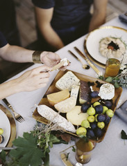 A table laid with a white cloth and place settings seen from above. An organic cheese board with soft and hard cheeses and figs. Two people sitting at the table.