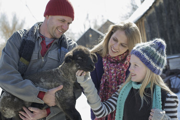 Winter scenery with snow on the ground. A man holding a young lamb, and a child stroking its chin.