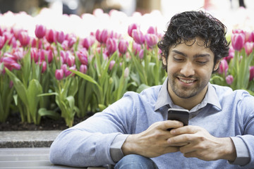 Urban Lifestyle. A man in the park, using his mobile phone. A bed of pink flowering tulips in the background.