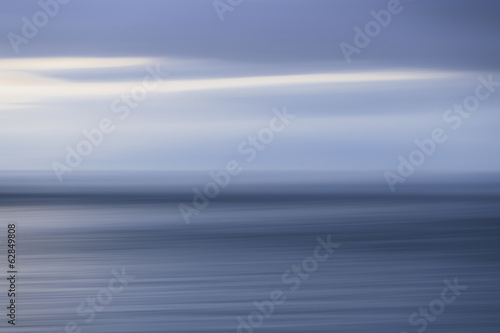 The sea and sky over Puget Sound in Washington, USA. The horizon with light cloud layers above.