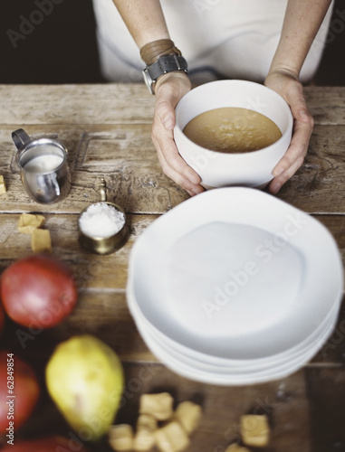 A domestic kitchen tabletop. A stack of white plates and fresh pears and a stack of sugar cubes. A bowl of  fudge sauce.