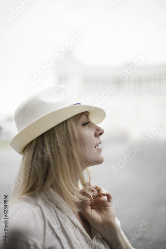A woman with blonde hair wearing a cream panama hat.