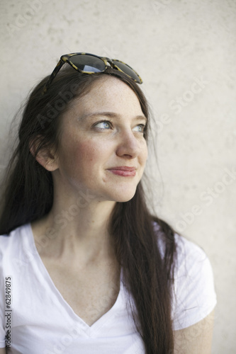 A young woman with long brown hair and sunglasses perched on her head. Wearing a white teeshirt.