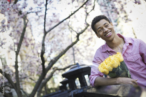 City life. A young man in the park in spring, holding a bunch of yellow roses.