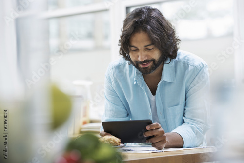 An office or apartment interior in New York City. A bearded man in a turquoise shirt using a digital tablet.