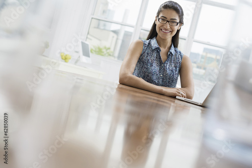 Business people. The office in summer. A young woman sitting comfortably in a quiet airy office environment. Using a laptop.