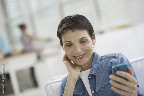 Professionals in the office. A light and airy place of work. A mature woman in a blue denim shirt looking at a blue smart phone.