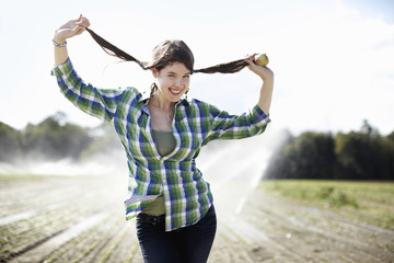 A girl in a green checked shirt with braids standing in a field with sprinklers working in the background.