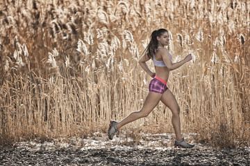 A woman running through a stand of tall grasses, growing taller than she is. Brown coloured shore grasses with feathery seedheads.
