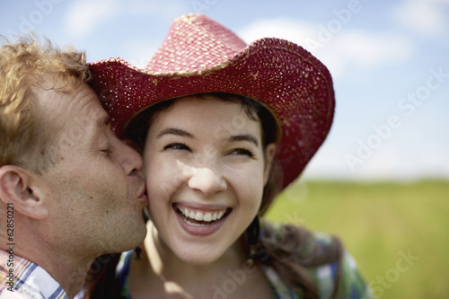A young woman in a wide-brimmed pink hat, being kissed on the cheek by a young man.