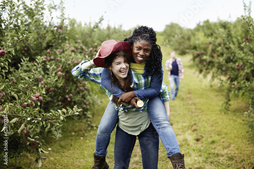Rows of fruit trees in an organic orchard. A young woman giving another a piggyback.