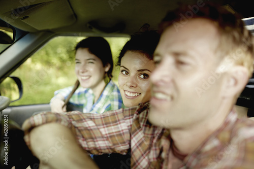 Three passengers in the cab of a pickup truck. One young man driving. Two young women sitting beside him.
