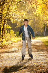 Boy on the roller on the autumn alley