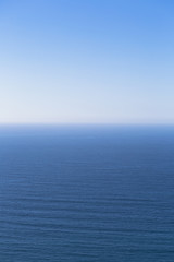 A view over the Pacific Ocean and a calm sea, merging into the blue sky.