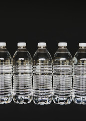 Row of clear, plastic water bottles filled with filtered water