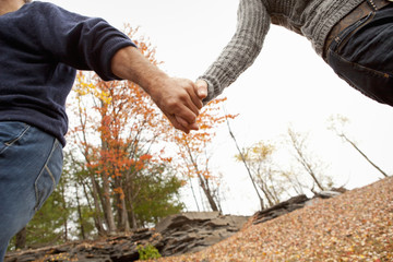 A couple, man and woman on a day out in autumn. Holding hands.