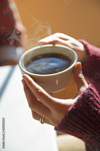 A woman holding a cup of hot coffee in her hands.