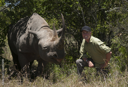 Art Wolfe, photographer kneeling next to a white rhinoceros in Kenya.