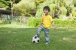Cute little boy with football standing at park
