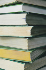 A stack of old hard cover books, with worn edges and paper that is stained or yellowed with age and use.