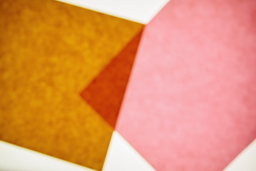 Two pieces of recycled construction paper,  brown and pink with a small overlapping triangle.
