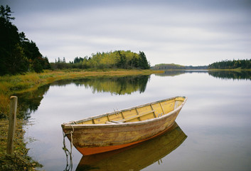 A small wooden dory or rowing boat moored on flat calm water, in Savage harbour on Prince Edward Island in Canada.