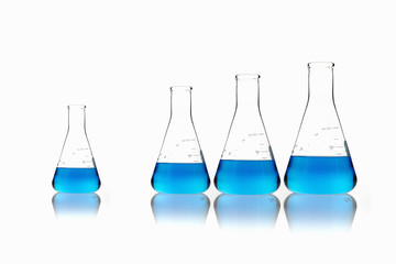 Conical glass scientific flasks holding blue liquids. Lined up in size order, with one set apart.