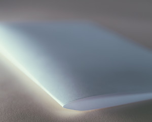 A folded piece of white recycled paper, close up.