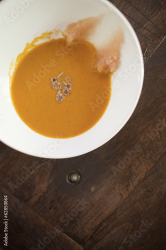 A white china bowl with a creamy soup and garnish, viewed from above. A rouille puree on the side of the dish.
