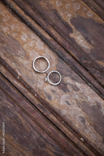 Platinum wedding rings . Two rings on a worn scrubbed stained wooden surface.