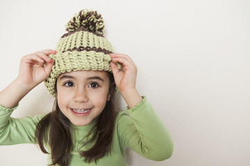 A young child with long brown hair, wearing a knitted hat with a pompom, peering from underneath the brim.