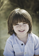 Young boy with brown hair and freckles, wearing blue shirt.