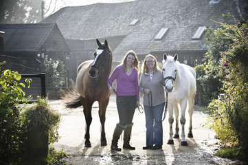 Two women standing outside a stable with two horses.