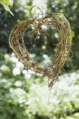 A heart shape made out of woven twigs, hanging from a tree. Simple decorations.